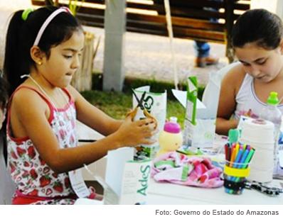 duas alunas mexendo com materiais recicláveis
